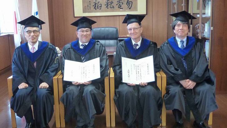 Four professors in doctoral gowns